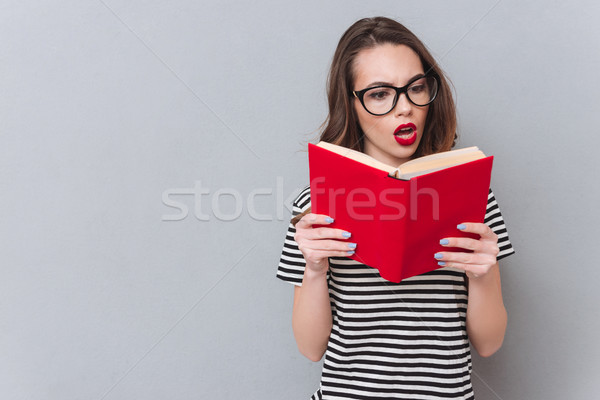Confused young lady standing over grey wall reading book. Stock photo © deandrobot