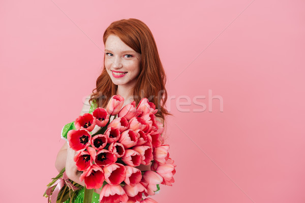 Smiling ginger woman holding bouquet of flowers Stock photo © deandrobot