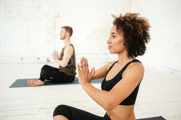 Side view of young african woman doing yoga Stock photo © deandrobot