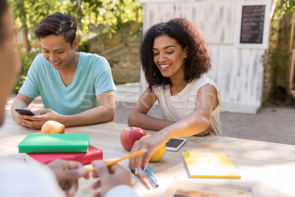 Happy young multiethnic group of friends students talking Stock photo © deandrobot