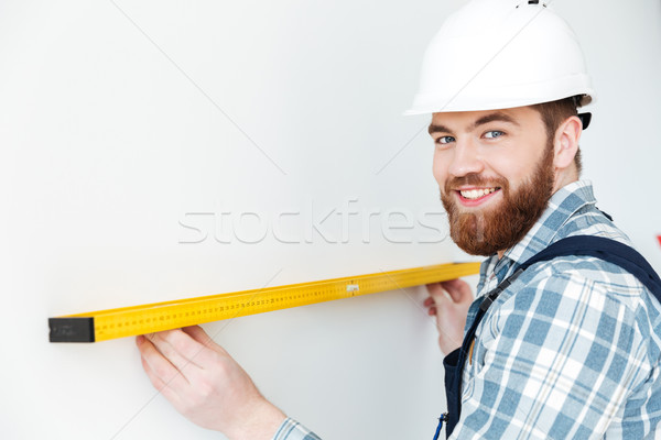 Young man builder standing in new flat make repair Stock photo © deandrobot