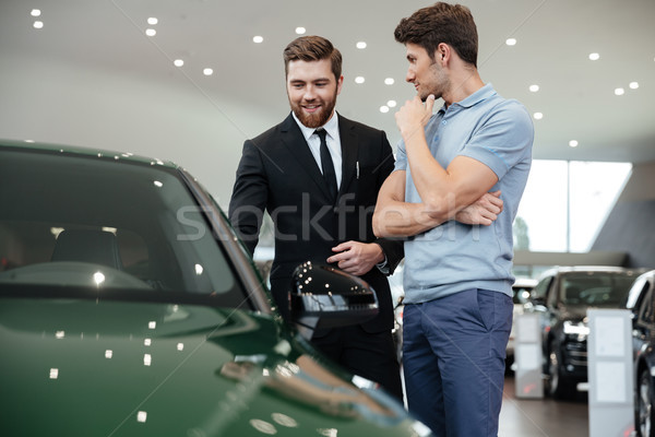 Stock photo: Young male car salesman showing a new car