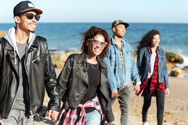 Group of happy african friends walking outdoors at beach. Stock photo © deandrobot