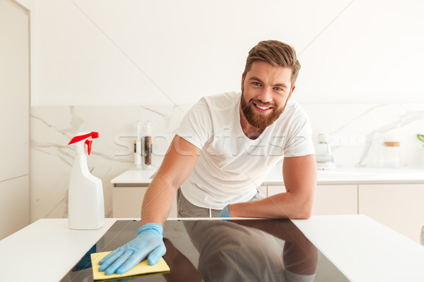 Handsome casual bearded man wipes a stove on kitchen Stock photo © deandrobot