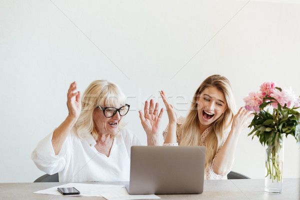 Surprised young lady sitting at home with her grandmother Stock photo © deandrobot
