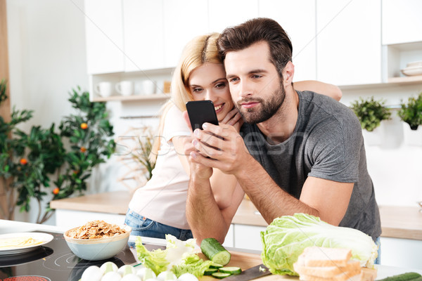 Happy smiling couple using mobile phone to find a recipe Stock photo © deandrobot