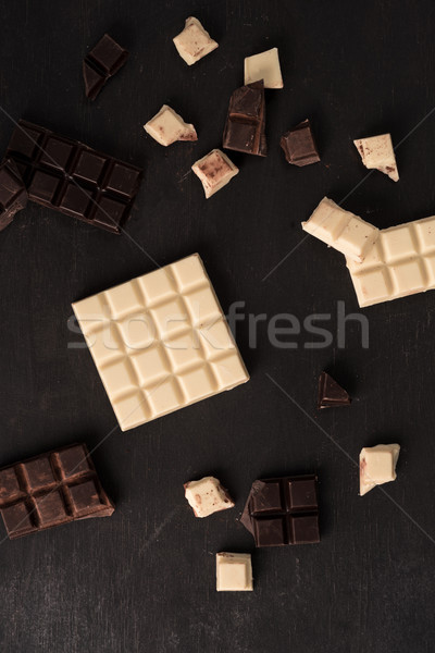 Top view of white and dark crashed chocolate bar tiles Stock photo © deandrobot