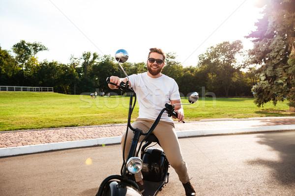 Happy bearded man in sunglasses sitting on modern motorbike Stock photo © deandrobot
