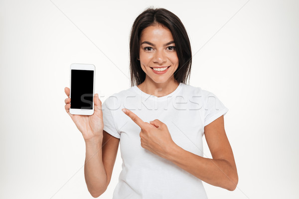 Portrait of a pretty woman presenting blank screen mobile phone Stock photo © deandrobot