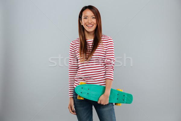Szczęśliwy asian kobieta sweter deskorolka Zdjęcia stock © deandrobot