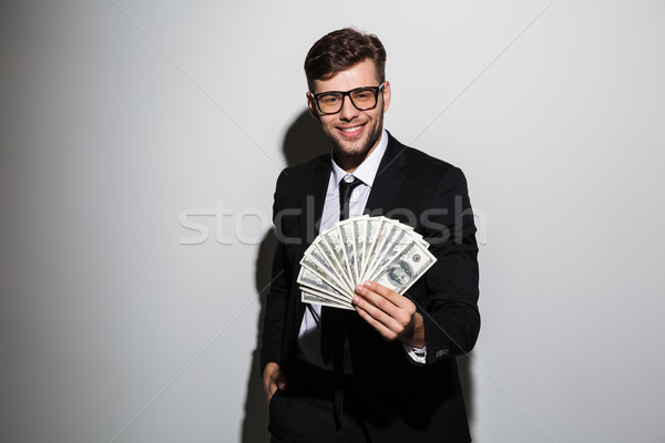 Cheerful guy in formal wear showing bunch of money, looking at c Stock photo © deandrobot