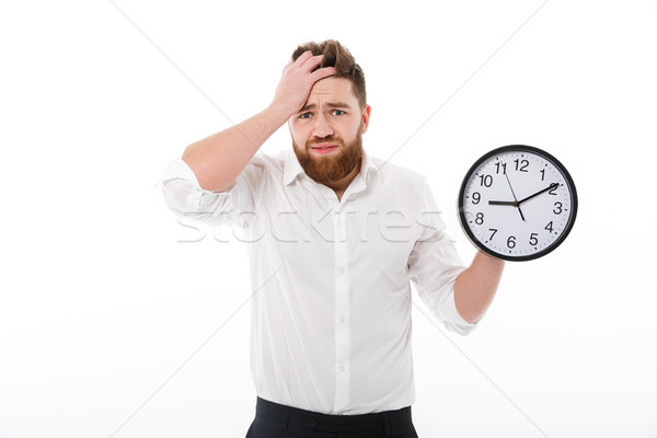 Confused bearded man in business clothes holding clock Stock photo © deandrobot