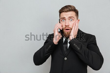 Carefree bearded business man holding finger in his nose Stock photo © deandrobot