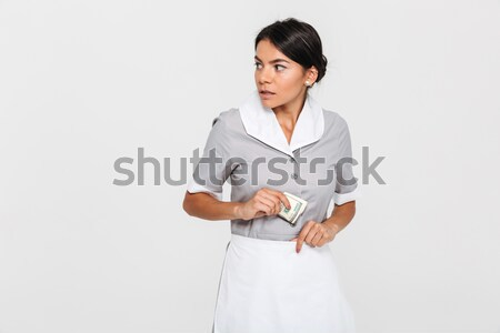 Close-up portrait of young concerned maid in uniform hiding doll Stock photo © deandrobot