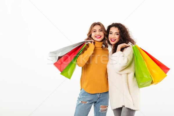 Due felice ragazze pacchetti guardando fotocamera Foto d'archivio © deandrobot