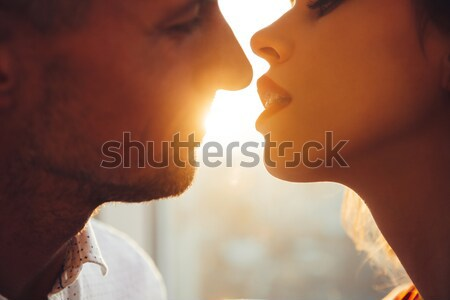 Cropped photo of young lovers kissing near window at home Stock photo © deandrobot