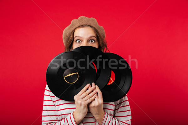 Portrait of a young woman wearing beret holding vinyl disks Stock photo © deandrobot