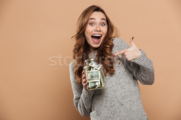 Happy attractive brunette girl in gray woolen sweater pointing w Stock photo © deandrobot