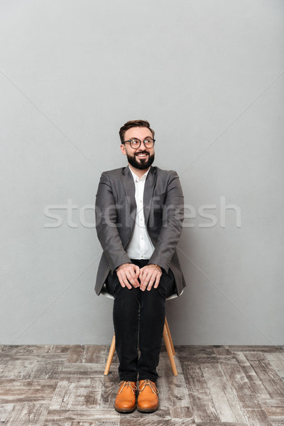 Full-length portrait of young man in jacket sitting on chair put Stock photo © deandrobot