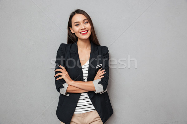 Pleased asian business woman with crossed arms looking at camera Stock photo © deandrobot