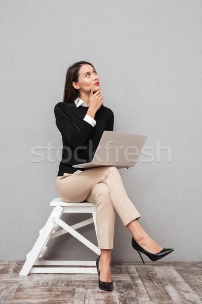 Tam uzunlukta görüntü dalgın gülümseyen kadın iş elbise Stok fotoğraf © deandrobot