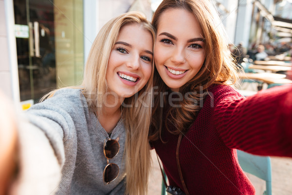 Two pretty smiling girls taking a selfie while sitting together Stock photo © deandrobot