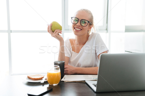 Cheerful lady with apple sitting in kitchen and looking camera Stock photo © deandrobot