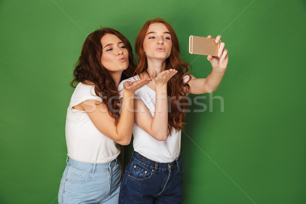 Image of two flirty women with ginger hair taking selfie on smar Stock photo © deandrobot