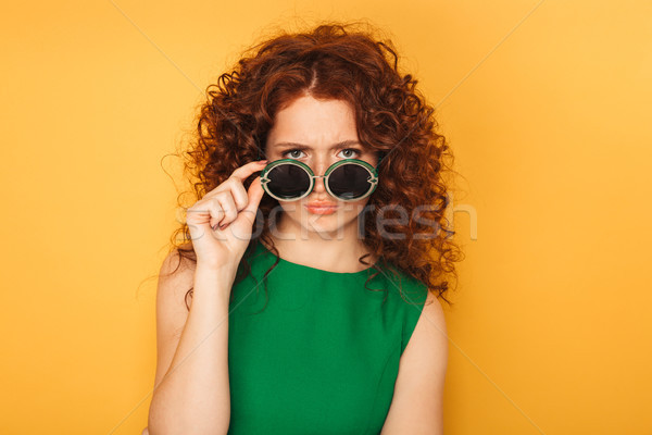 Portrait of an upset redhead woman in dress Stock photo © deandrobot