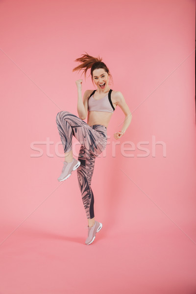 Full length image of Cheerful sportswoman screaming and rejoices Stock photo © deandrobot