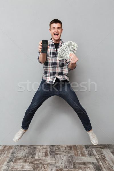Сток-фото: портрет · возбужденный · молодым · человеком · деньги
