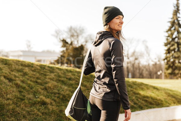Photo of joyous athletic girl in black sportswear, walking with  Stock photo © deandrobot