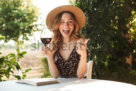Young woman sitting in cafe drinking wine waving to friends. Stock photo © deandrobot