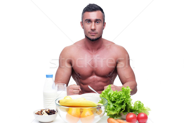 Happy muscular man sitting at the table with healthy food  Stock photo © deandrobot