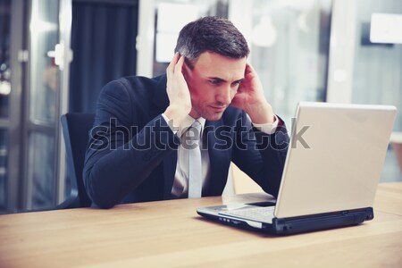 Pensive businessman sitting with laptop at office Stock photo © deandrobot