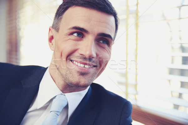 Portrait of a handsome smiling businessman in suit looking away Stock photo © deandrobot