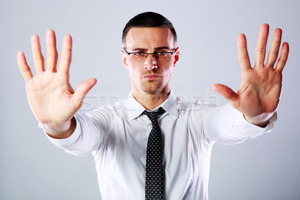 Confident businessman gesturing stop sign with both hands on gray background Stock photo © deandrobot