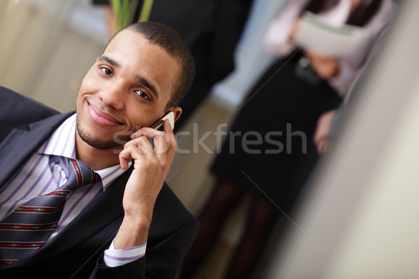 Happy african-american businessman on phone with his team working behind Stock photo © deandrobot