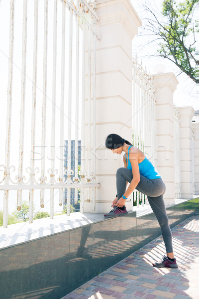 Jonge vrouw runner schoenveters portret zon Stockfoto © deandrobot