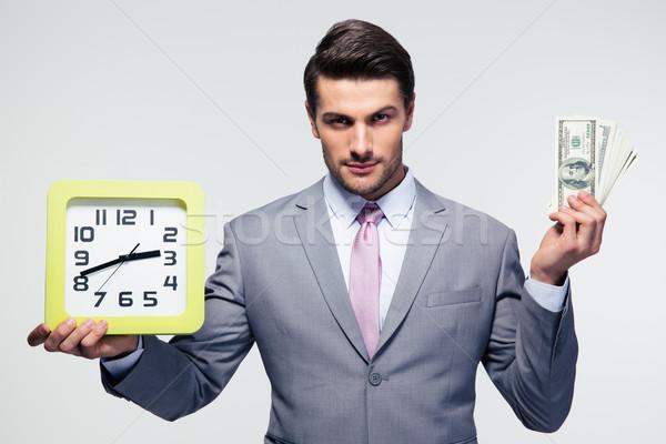 Businessman holding money and clock Stock photo © deandrobot