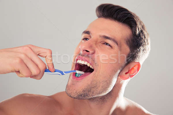 Young man brushing teeth Stock photo © deandrobot
