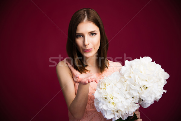 Beautiful woman holding flowers and sending kiss  Stock photo © deandrobot