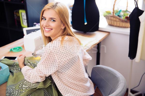Femme souriante machine à coudre souriant cute femme buanderie Photo stock © deandrobot