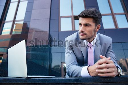 Businessman talking on the phone and using laptop  Stock photo © deandrobot