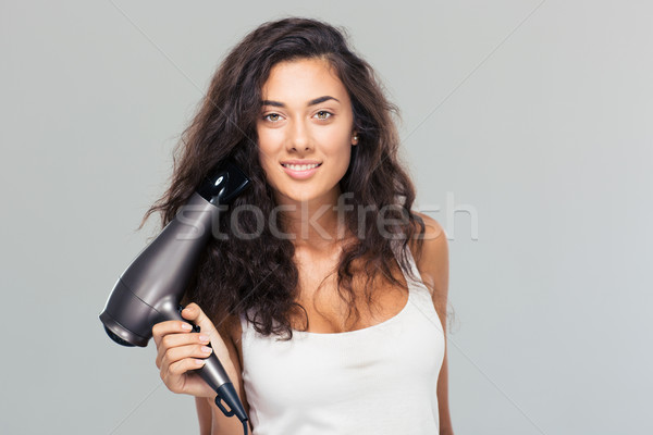 Smiling woman holding hairdryer Stock photo © deandrobot
