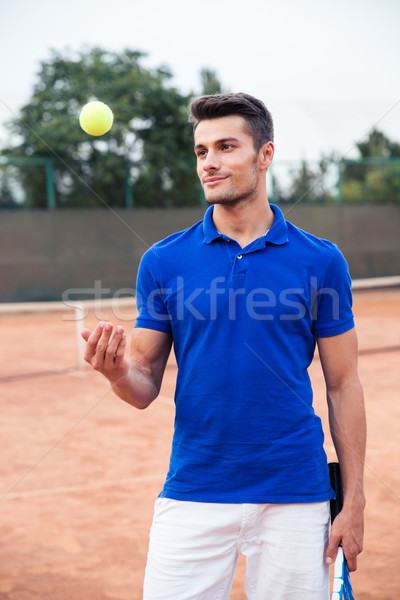 Male tennis player standing outdoors Stock photo © deandrobot
