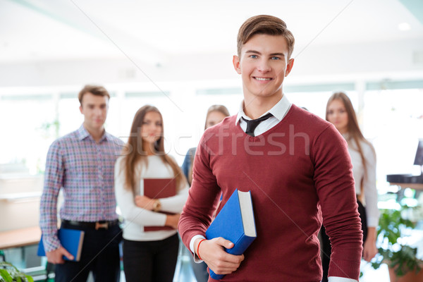 Male student standing with classmates on background Stock photo © deandrobot