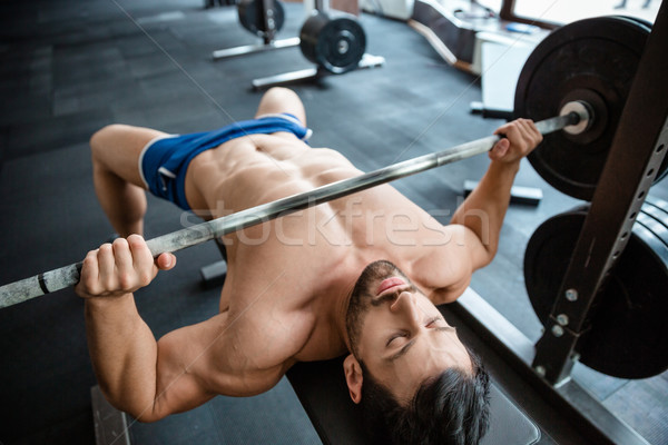 Muscular man doing bench press Stock photo © deandrobot