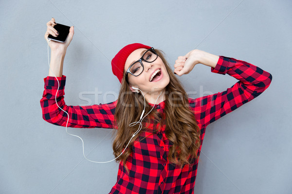 Woman listening music in headphones and dancing Stock photo © deandrobot