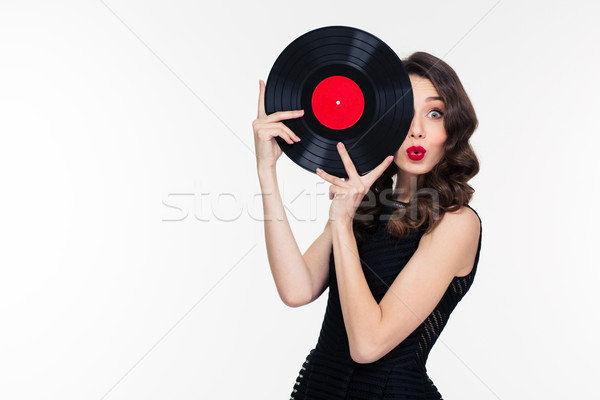 Playful beautiful woman covered half of face with vinyl disc Stock photo © deandrobot